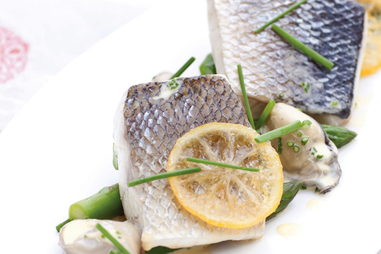 Poached sea bass, confit lemon butter, asparagus and Royal Bay oysters