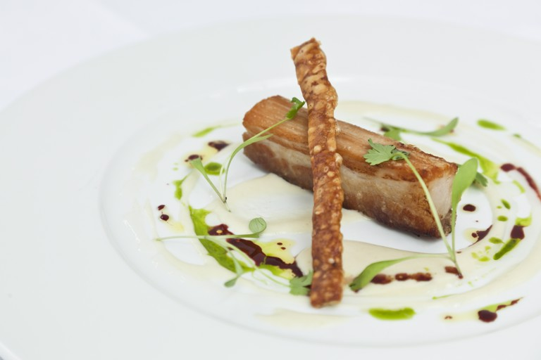Slowly braised belly of pork with apple soup, garlic purée and Port jus