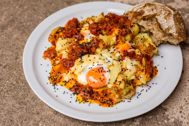 Potatoes with spiced Sugo, curds and fried eggs