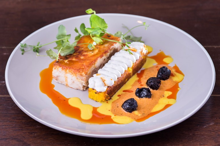 Chicken pachamanca with yellow cuzco corn and Pisco-infused prunes
