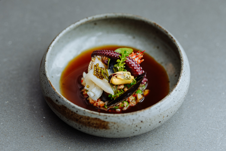 Rockpool of local seafood with sea vegetables, ginger and shellfish consommé