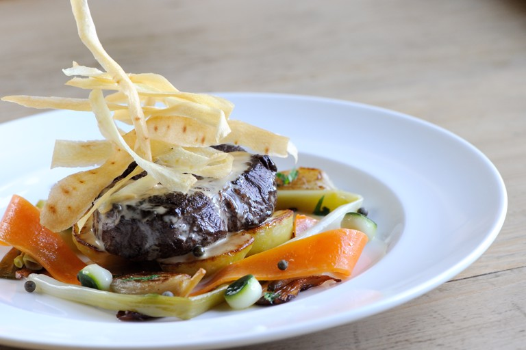 Beef fillet with roasted shallots, sauté potatoes and green peppercorn sauce