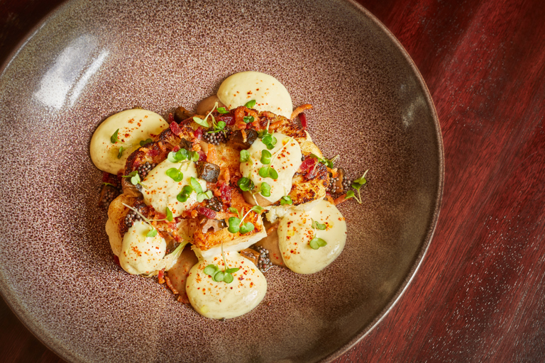 Cauliflower steak with Black Bomber cheddar, bacon and pickled walnuts