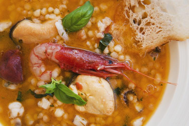 Seafood soup with fregula, basil and citrus