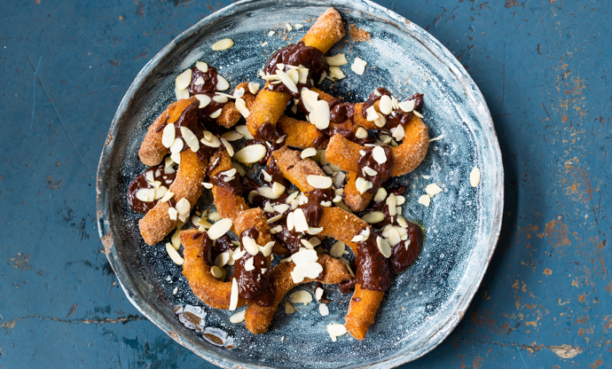 Churros with chocolate sauce and almonds