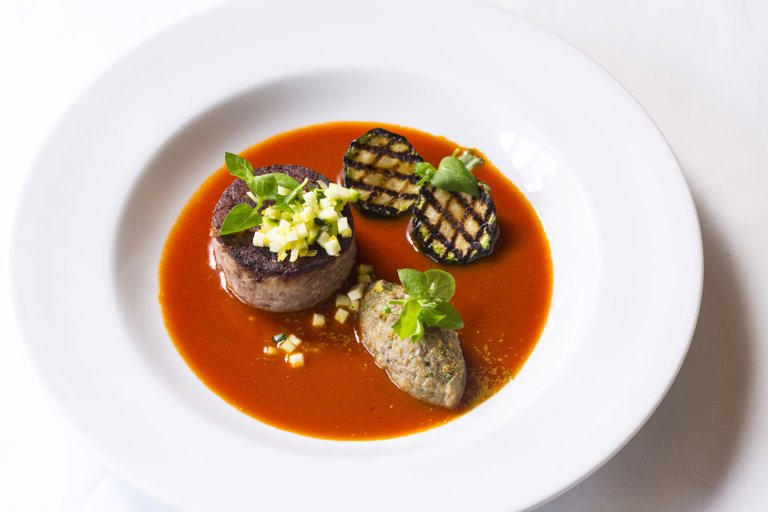Spiced goat with tomato fondue, aubergine purée and courgette
