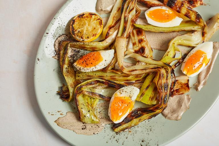 Charred leeks with leek ash crème fraîche, burnt citrus dressing and soft egg