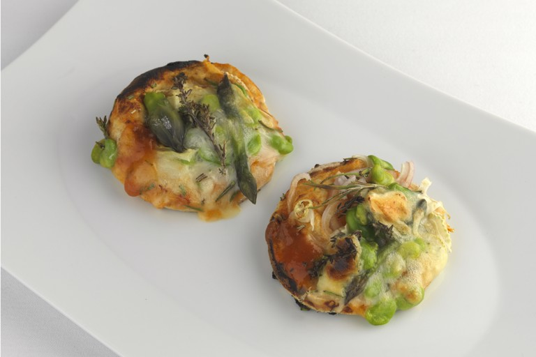 Barbecued pizza topped with asparagus, broad beans and fennel