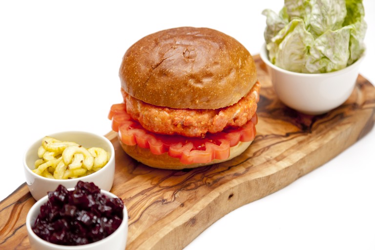 Alaska salmon burger with beetroot chutney, dill pickles and salad with sour cream dressing
