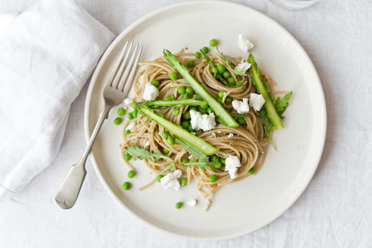 Whole wheat spaghetti with rocket pesto, asparagus, peas and goat's cheese