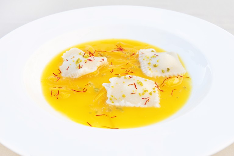 Almond ravioli filled with cassata on top of orange soup