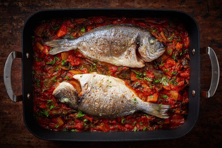 Whole baked bream with tomato and chard
