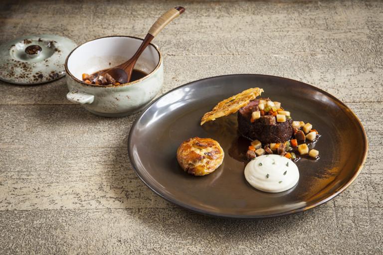 Venison loin with parsnip purée, suet dumpling and sausage casserole