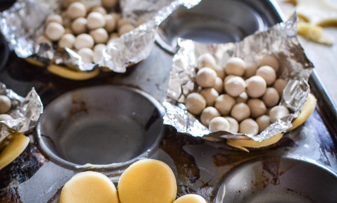 Lay a little foil on top of the pastry rounds and then fill each with some baking beans