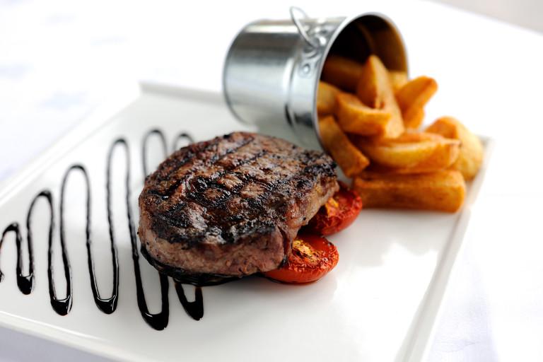 Rib-eye steak with chunky chips, field mushrooms and vine tomatoes