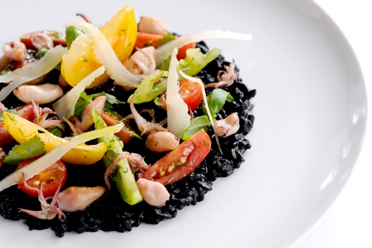Risotto nero with sautéed squid and tomatoes